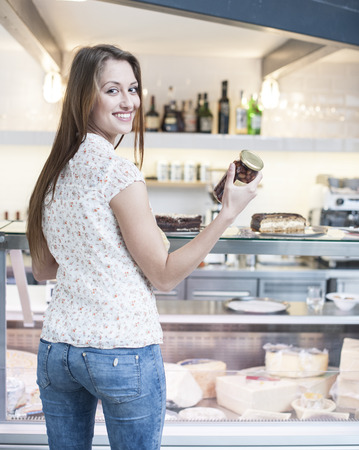 czech women: Rear view of smiling woman holding chocolate jar in front of display cabinet at cafe