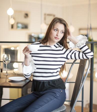 czech women: Thoughtful young woman looking away while having coffee at cafe