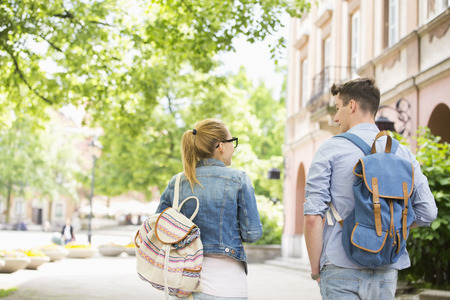 student: Rear view of young college friends talking while walking in campus