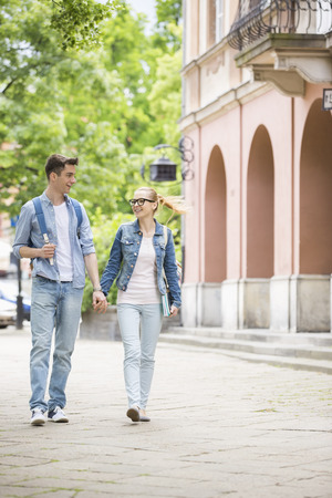 18 19 years: Full length of young college couple talking while walking in campus