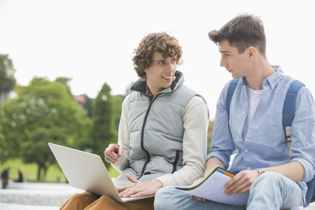 18 19: Young male college friends with laptop studying together in park