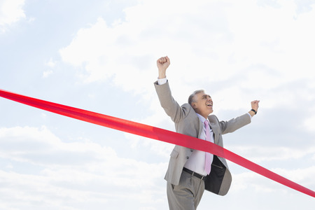 40 44 years: Cheerful businessman crossing finish line against sky LANG_EVOIMAGES