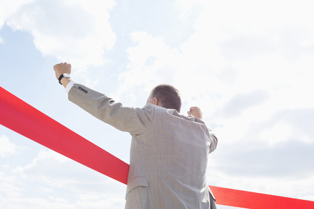 40 44 years: Rear view of businessman crossing finish line against sky