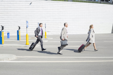 40 44 years: Side view of businesspeople with luggage walking on street