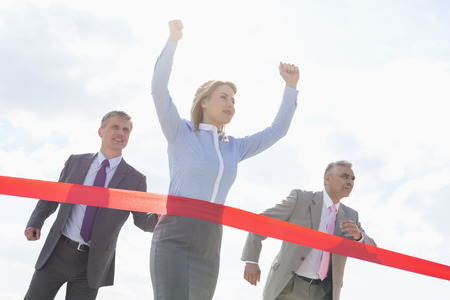 40 44 years: Businesswoman crossing finishing line with colleagues in background LANG_EVOIMAGES