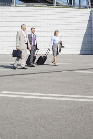 40 44 years: Businesspeople with luggage walking on street