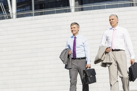 40 44 years: Middle-aged businessmen with briefcases against wall