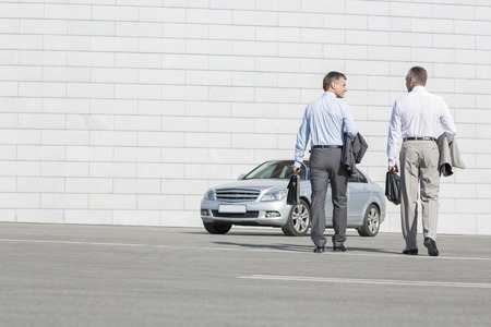 40 44 years: Rear view of businessmen carrying briefcases while walking towards car on street