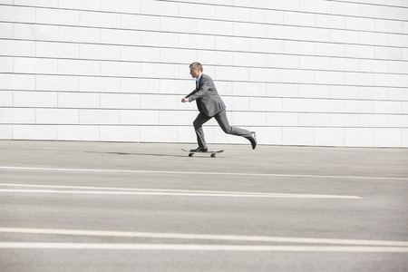 40 44 years: Side view of businessman skateboarding on street LANG_EVOIMAGES