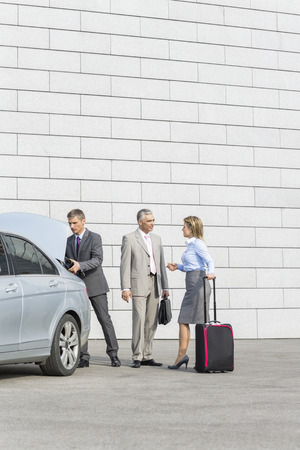 40 44 years: Businesspeople with luggage communicating outside car on street