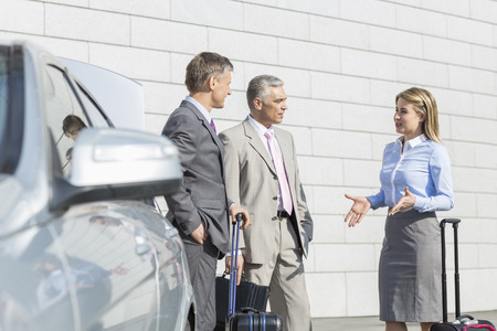 40 44 years: Businesspeople with luggage discussing outside car