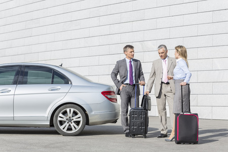 40 44 years: Businesspeople with luggage discussing outside car on street LANG_EVOIMAGES
