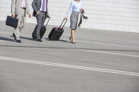 40 44 years: Low section of businesspeople with luggage walking on street