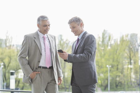40 44 years: Businessmen using cell phone together outdoors