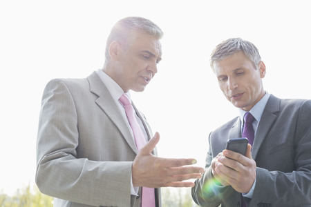 40 44 years: Businessmen discussing over mobile phone outdoors