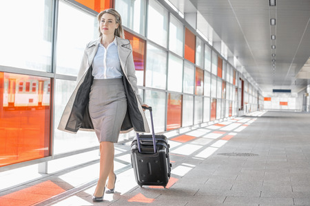 woman  glasses: Full length of young businesswoman with luggage walking in railroad station