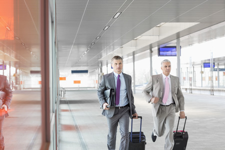 Middle aged businessmen with luggage rushing on railroad platform Stock Photo