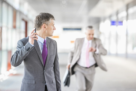 Middle aged businessman looking at colleague running in railroad station