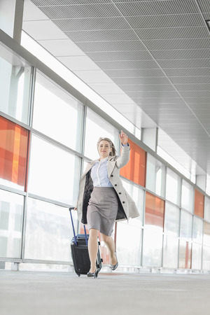 late 20s: Full length of young businesswoman with luggage rushing in railroad station