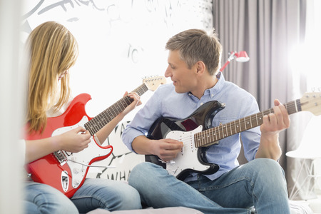 girl playing guitar: Middle-aged man with daughter playing guitars at home