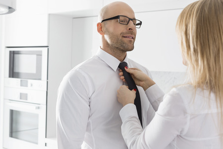 Woman adjusting businessmans tie at home Stock Photo