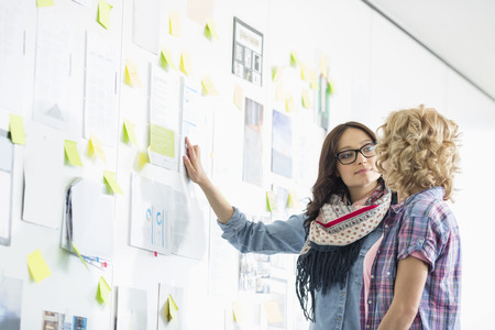 two years: Creative businesswomen discussing over papers stuck on wall in office