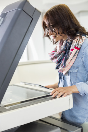 photocopier: Businesswoman using photocopier in creative office LANG_EVOIMAGES
