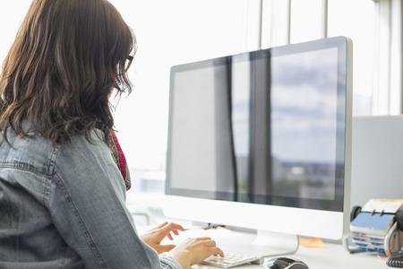 Achteraanzicht van zakenvrouw met behulp van desktop computer in creatieve kantoor