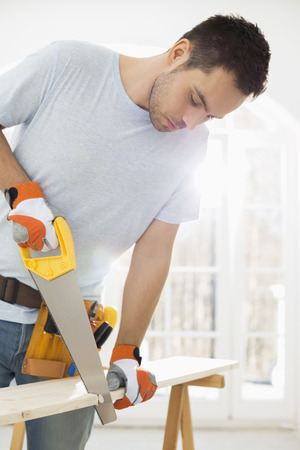 Man sawing wood in new house LANG_EVOIMAGES