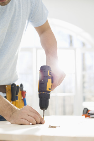midsection: Midsection of man drilling nail on table