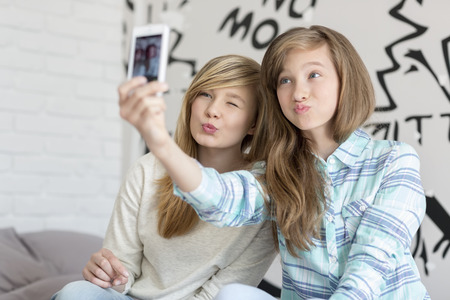cute girl with long hair: Cute sisters pouting while taking photos with smart phone at home