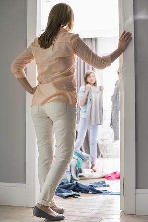 mother and teen daughter: Full-length rear view of mother watching daughters trying on clothes in room LANG_EVOIMAGES