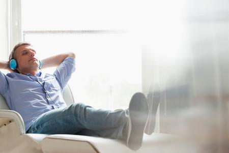Full-length de Homem de meia idade relaxado a ouvir m LANG_EVOIMAGES