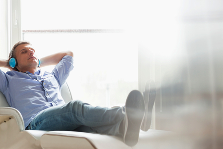 people sitting on chair: Full-length of relaxed Middle-aged man listening to music at home