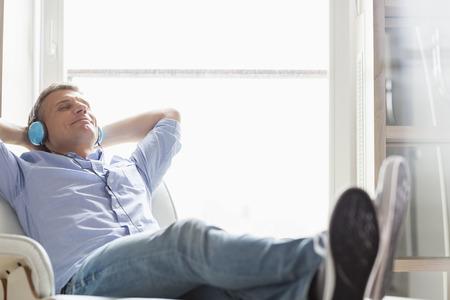 relajado: De longitud completa de hombre de mediana edad relajada escuchando m�sica en casa