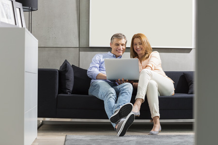 furniture hardware: Full-length of smiling couple using laptop on sofa
