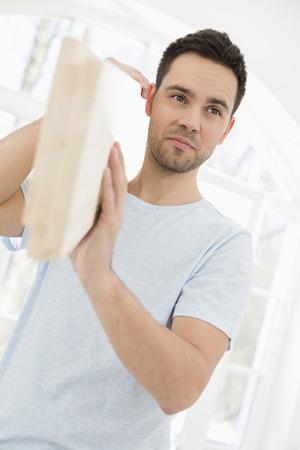 shoulder carrying: Mid-adult man carrying wooden plank on shoulder