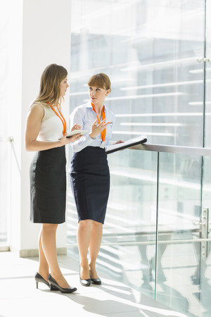 business communication: Full-length of businesswomen discussing over tablet PC while standing by railing in office LANG_EVOIMAGES