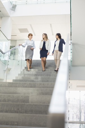 moving down: Businesswomen conversing while moving down steps in office LANG_EVOIMAGES