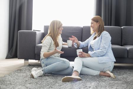 幸せな母と娘のリビング ルームでコーヒーを持ちながら話しています。