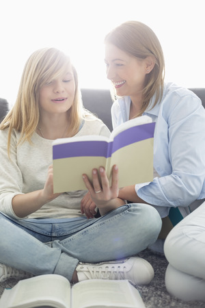 child studying: Mother assisting daughter in homework at home