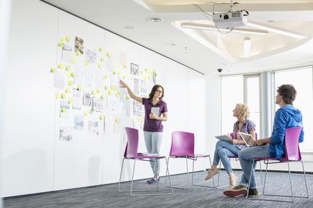 comunicação: Mulher de negócios que dá a apresentação aos colegas no espaço de escritórios criativo