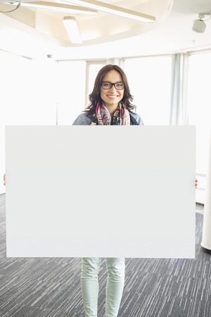 18 19 years: Portrait of happy businesswoman holding blank sign in creative office