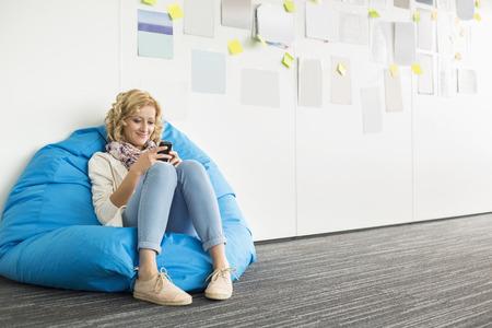 silla: Sonriente mujer de negocios utilizando tel�fono m�vil en la silla pelotita en la oficina creativa