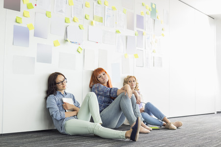 18 19 years: Tired businesswomen sitting on floor in creative office LANG_EVOIMAGES