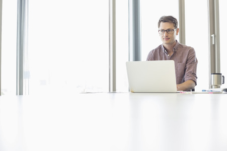 Thoughtful businessman looking away while using laptop at desk in creative office