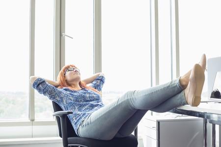 In voller Länge der Geschäftsfrau Entspannung mit den Füßen am Schreibtisch im Büro kreative