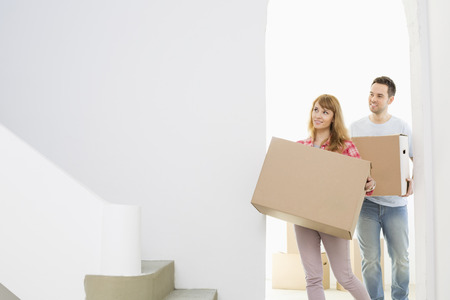 moving in: Couple carrying moving boxes