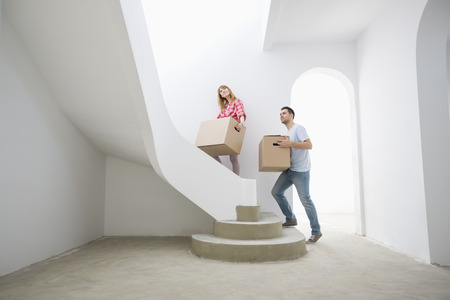30 34 years: Couple carrying cardboard boxes up stairs in new house LANG_EVOIMAGES