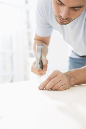 Mid-adult man nailing in table Stock Photo